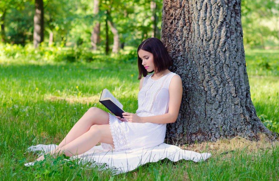木の下で読書をする女性