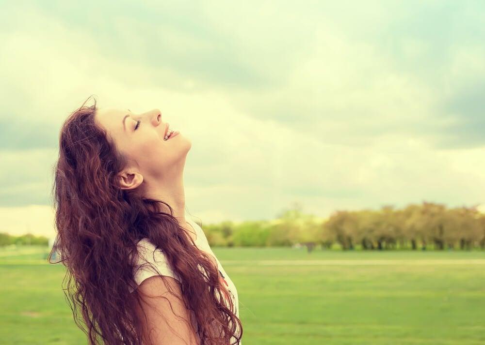 草原で空を仰ぐ女性