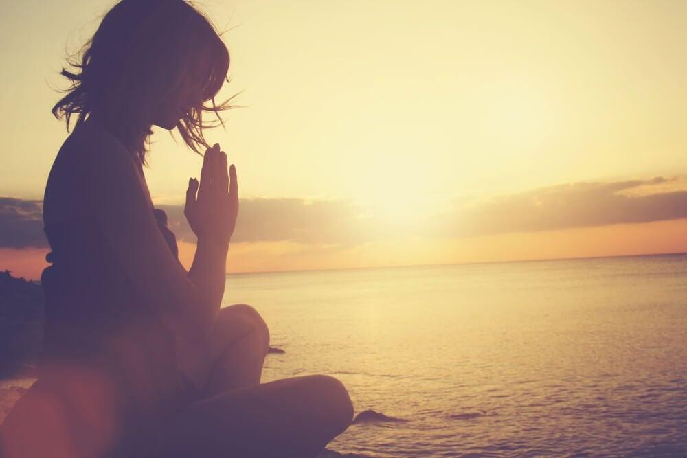 夕焼けの海岸で祈る女性
