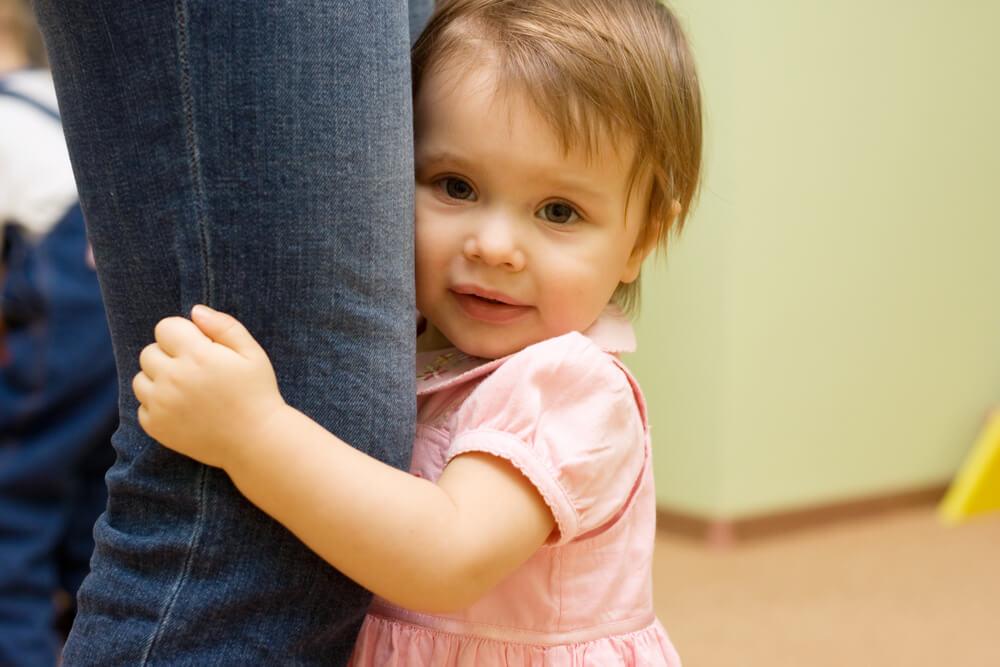 親の脚にしがみつく子供