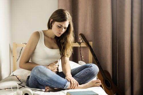 ベッドで腹部を抑える女性