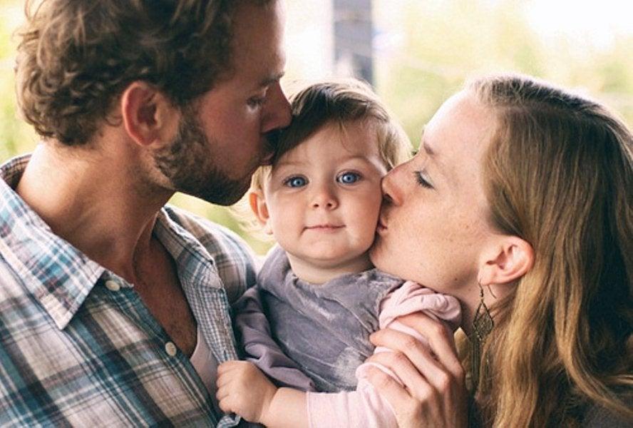 子供にキスをするカップル
