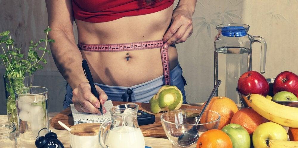キッチンでウエストを測る女性