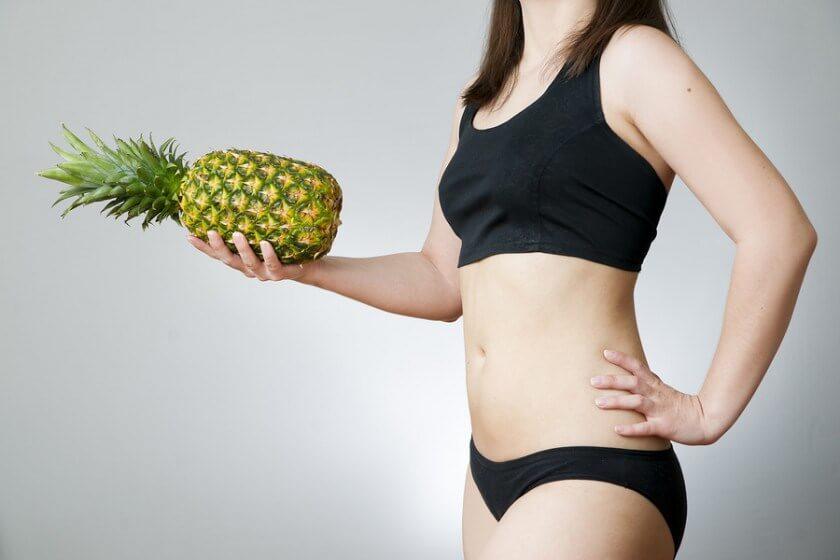 パイナップルを片手に持つ女性