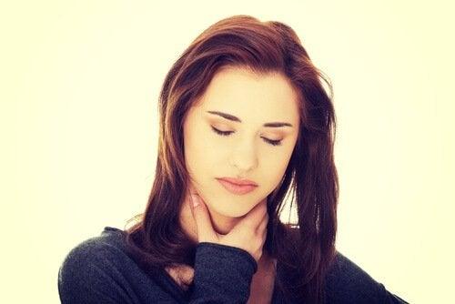 首を抑え目を閉じる女性