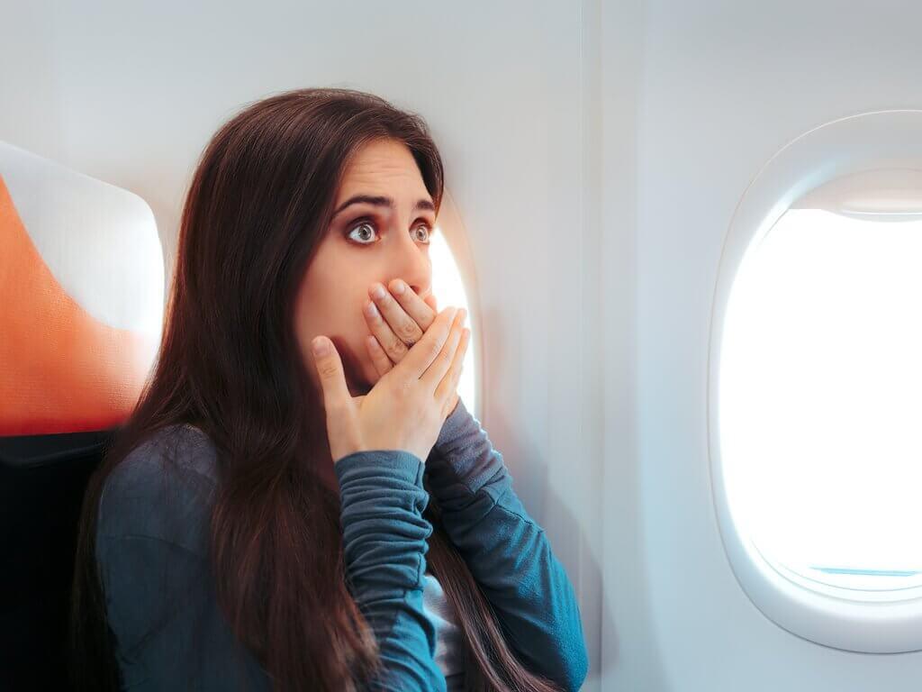 飛行機で口を抑える女性 吐き気を抑える
