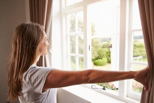 窓を開ける女性 カビを除去する