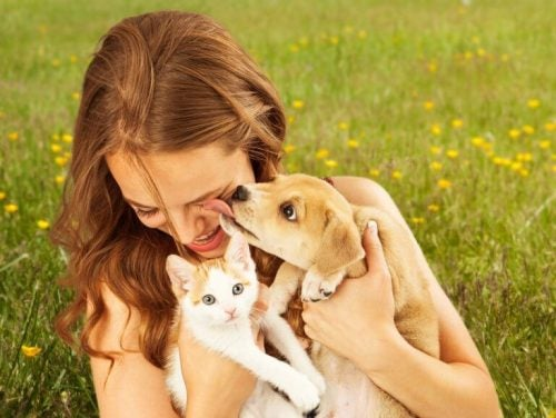 猫と犬を抱える女性