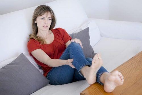 ソファで脚を触る女性