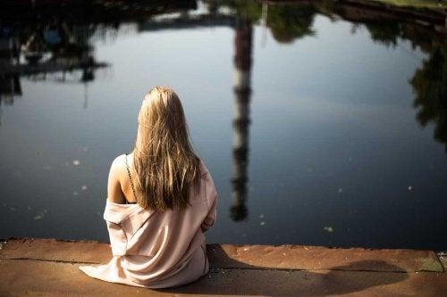 水辺に座る女性 孤独を感じる理由