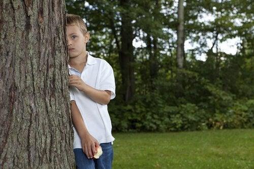 木の後ろに立つ子供