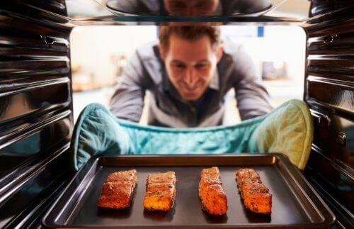 オーブンから料理を取り出す男性