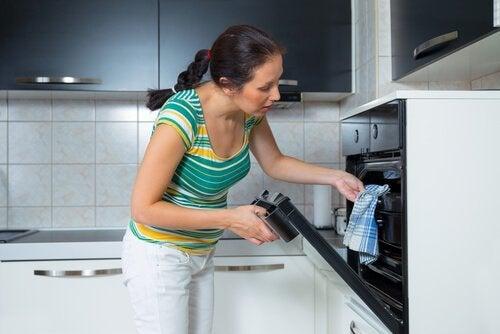 オーブンを使い調理する女性
