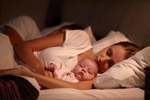 母親のそばで眠る赤ちゃん 赤ちゃん 睡眠 母親