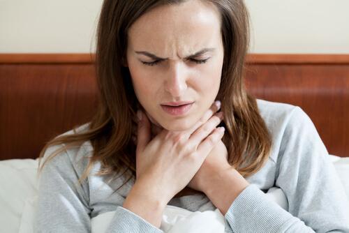 喉の痛みに苦しむ女性