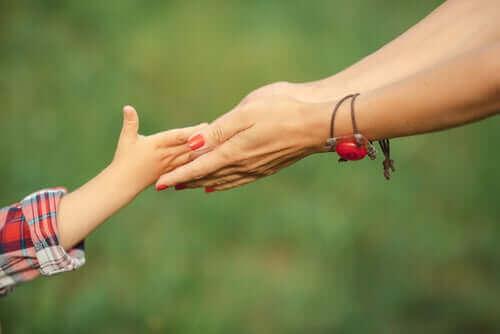 ペアレンティング:様々な子育てスタイルについて 子供の手を握る親