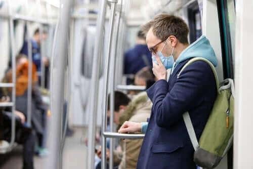 マスクをして電車に乗る人 新型コロナウイルスは表面でどのくらい生存しますか?
