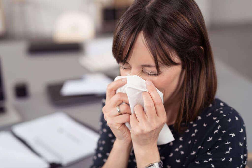 COVID-19のパンデミック:顔に触れないためのヒント くしゃみをする女性