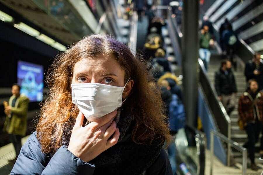 COVID-19のパンデミック:顔に触れないためのヒント マスクをつける女性