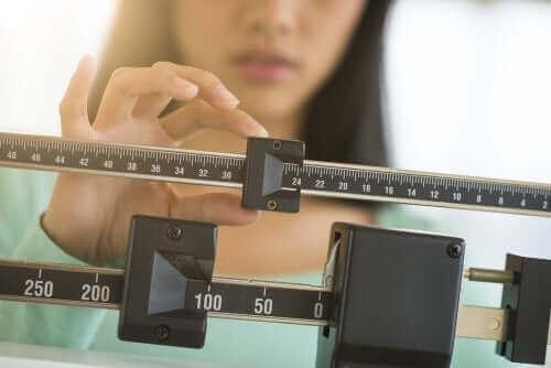 キャロブパウダー:6つの特性と利点 体重を測る女性