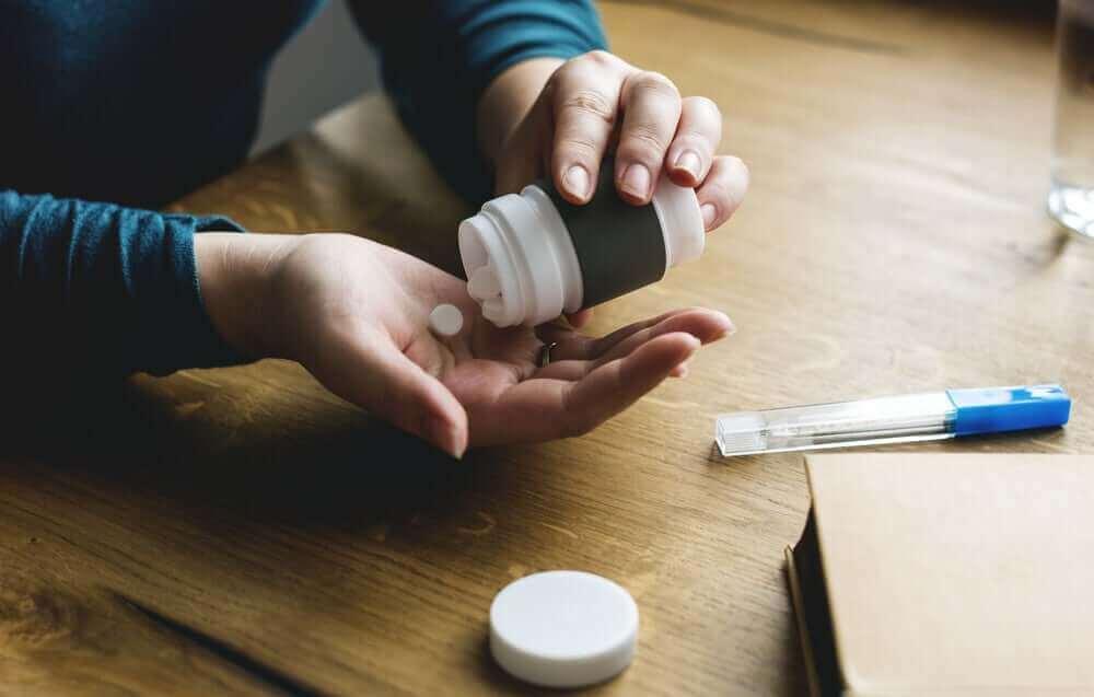 新型コロナウイルスとイブプロフェンは危険な組み合わせですか? 錠剤を飲む患者