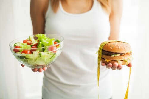 肥満の予防に役立つ食品のタイプとは? サラダとハンバーガーを持つ女性