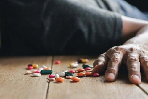 薬と床に倒れる男性 薬物中毒