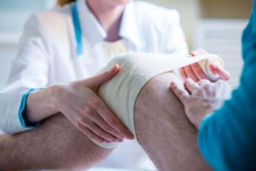 膝に包帯を巻く人